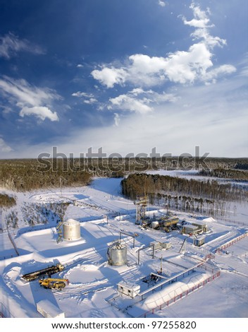 Oil and gas industry. Work of oil pump jack on a oil field..Construction site in wild winter forest. Building of petrochemical plant - stock photo