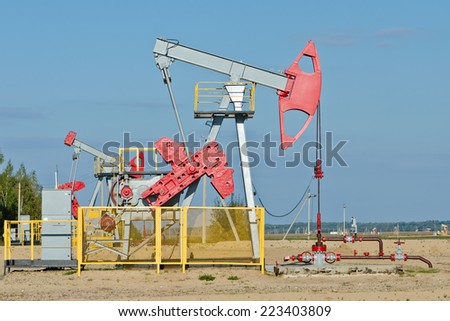 Oil and gas industry. Work of oil pump jack on a oil field. First pump in focus, shallow depth of field - stock photo