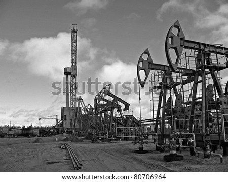 Oil and gas industry. Work of oil pump jack on a oil field. Rig. Black and white photo - stock photo