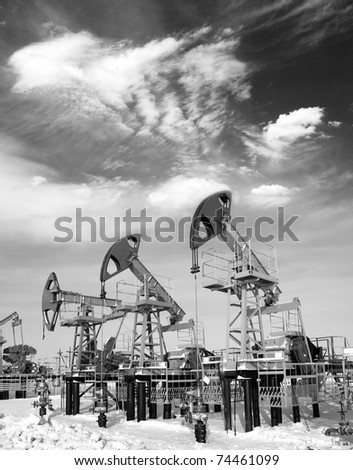 Oil and gas industry. Work of oil pump jack on a oil field. White clouds above oil field. Black and white photo