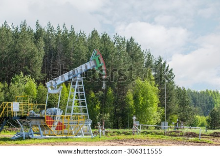 Oil and gas industry. Work of oil pump jack on a oil field. White clouds and blue sky. oil well pump. Oil and gas industry. Work of oil pump jack on a oil field.  - stock photo