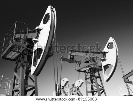 Oil and gas industry. Work of oil pump jack on a oil field. Wide Angle. Black and white photo - stock photo