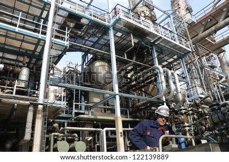 oil and gas power and energy industry. oil worker with pipelines machinery in foreground - stock photo