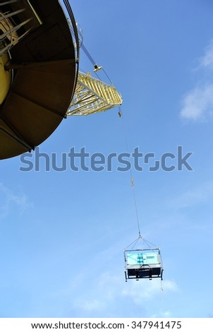 Oil and gas production rig platform pedestal crane lifting air compressor to supply work boat for transporting to port after using for wireline activities. - stock photo
