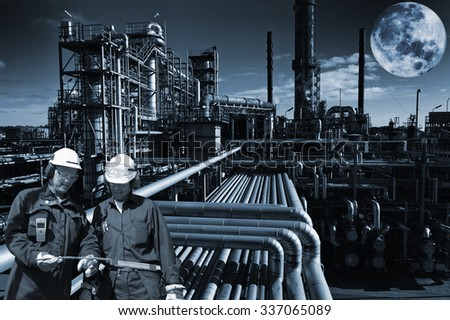 oil and gas refinery at night, large full moon hovering above - stock photo