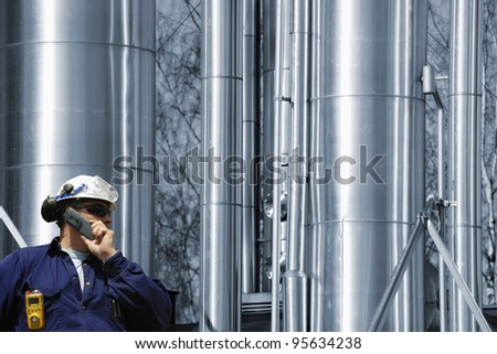 oil and gas refinery, engineer, worker talking in phone with large gas pipelines, tubes in background - stock photo