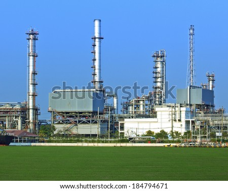 Oil and gas refinery with reflection on green field - Petrochemical factory  - stock photo