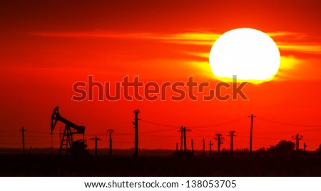 Oil and gas well profiled on bright solar disk - stock photo