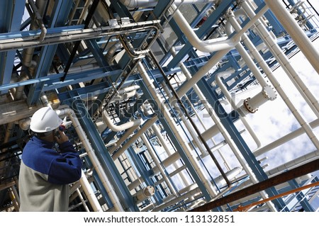 oil and gas worker pointing at giant pipeline construction, inside view of industry - stock photo