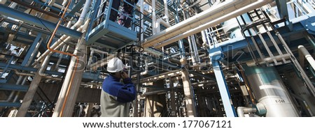 oil and gas worker pointing at large refinery construction, pipelines and pumps - stock photo