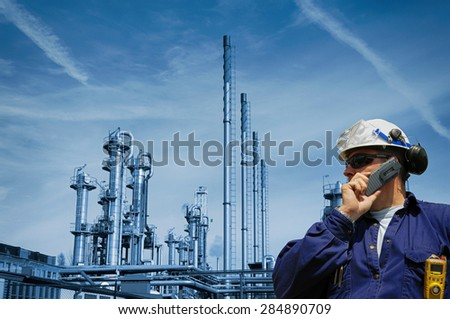 oil and gas worker with large refinery industry in background - stock photo