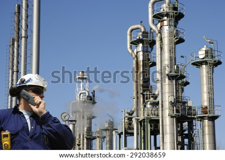 oil and gas worker with refinery towers in background - stock photo