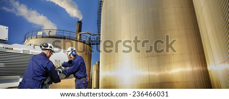 oil and gas workers and storage tanks - stock photo