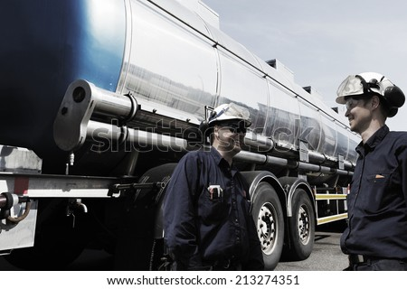 oil and gas workers fueling large fuel-truck, tanker inside refinery - stock photo