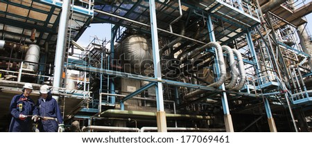 oil and gas workers inside large chemical installation, panoramic concept - stock photo