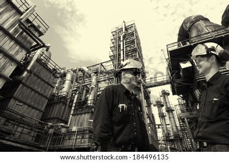 oil and gas workers inside large chemical refinery industry - stock photo