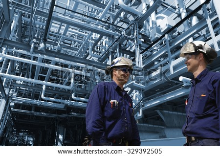 oil and gas workers inside refinery industry, pipelines constructions - stock photo