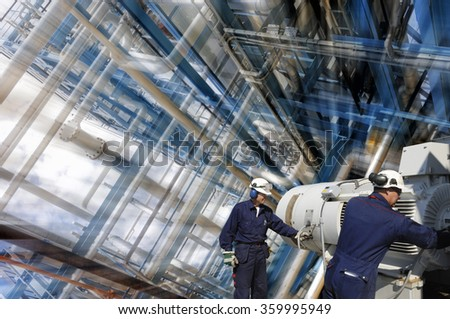 oil and gas workers with pipelines inside refinery, slight zoom effect - stock photo