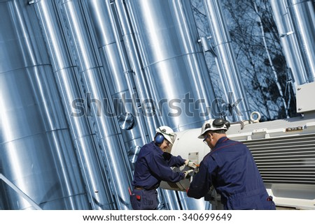 oil and gas workers with pump machinery in front of large horizontal pipelines - stock photo