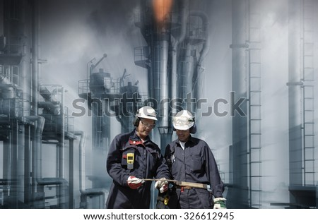 oil and gas workers with refinery in background, slight zoom effect - stock photo