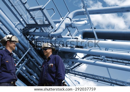 oil and gas workers with refinery pipelines in background - stock photo