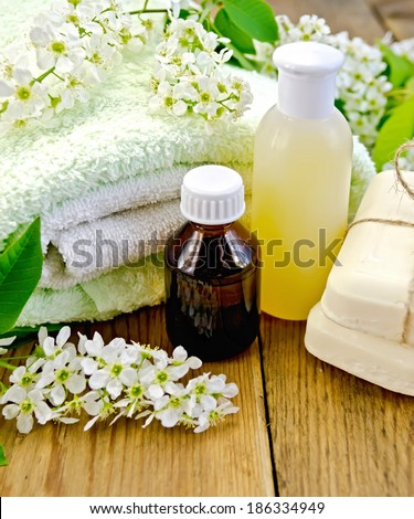 Oil and lotion bottles, soap, flowers bird cherry, a towel on the background of wooden boards - stock photo