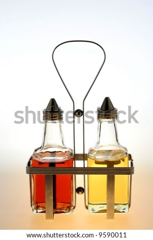 Oil and vinegar bottles in a wire rack. - stock photo