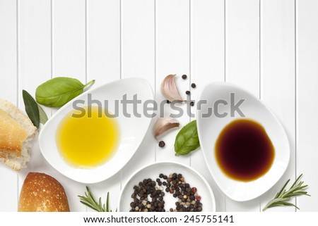 Oil and vinegar food background, with fresh bread, peppercorns and herbs over white wood panel. - stock photo