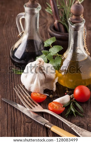 oil and vinegar in vintage bottles on wooden table, sliced tomatoes cherry with garlic, mint and rosemary in wooden mortar, and vintage silverware - stock photo
