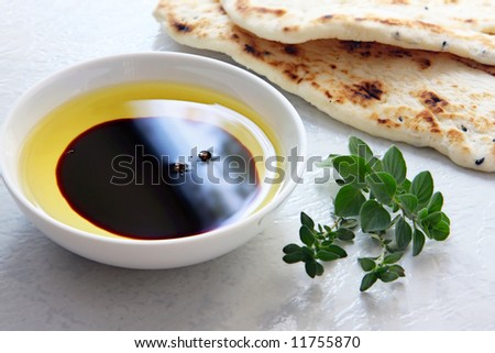 Oil and vinegar - small bowl of olive oil and balsamic vinegar, with dipping bread and fresh herbs. - stock photo