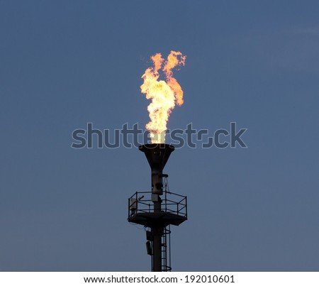 Oil burning torch against the blue sky