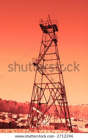 """Oil derrick with """"donkey"""" pump during sunset - stock photo"""