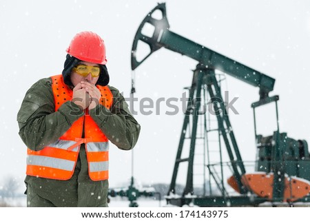 Oil Drill, field pump jack with snow storm and worker who feels cold. See more images and video from this series and Refinery series.