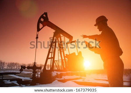 Oil Drill, field pumpjack silhouette with setting sun and worker. Lens Flare. See more images and video from this series and Refinery series.  - stock photo