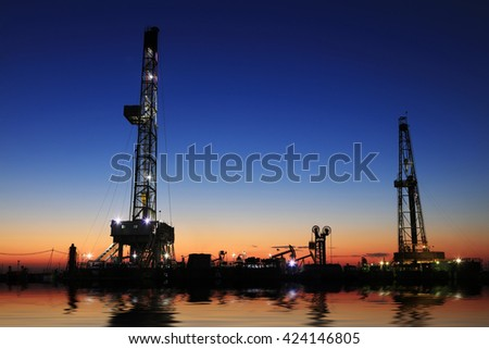 Oil drilling derrick and lights in oilfield