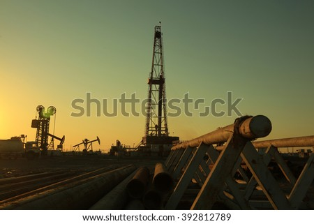 Oil drilling derrick and pipelines in oilfield - stock photo