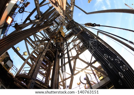 Oil Drilling Derrick with Top Drive, Drill Pipe, Kelly Hose With Fish Eye Perspective - stock photo