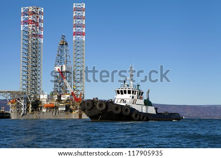 Oil drilling jack up rig with a tug boat in the Kachemak Bay near Homer Alaska on a sunny day. - stock photo