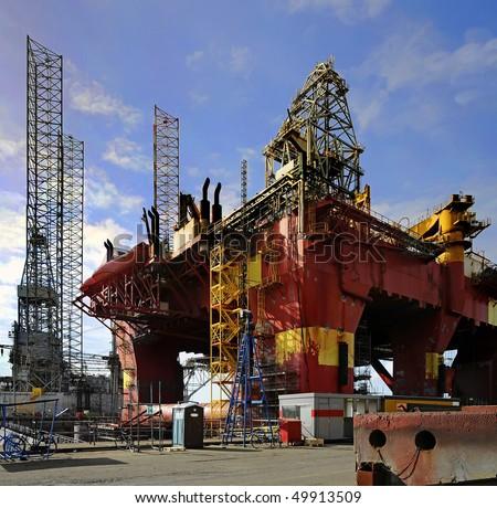 Oil drilling platform for repairs at shipyard - stock photo