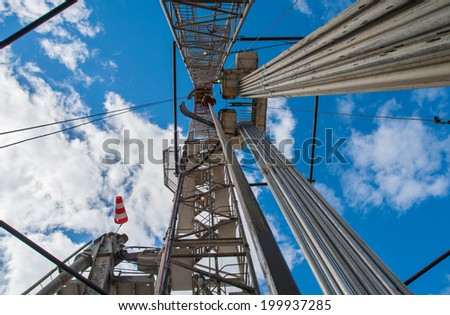 Oil drilling rig against a blue sky with clouds - stock photo