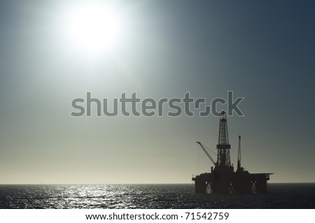 oil drilling rig far in the horizon.  Hard sun light silhouette. - stock photo