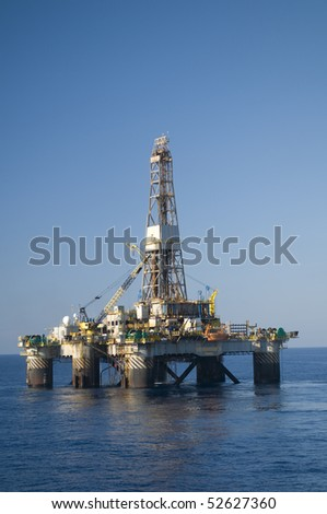 Oil drilling rig in offshore area.  Blue sky and calm seas.  Coast of Brazil - stock photo