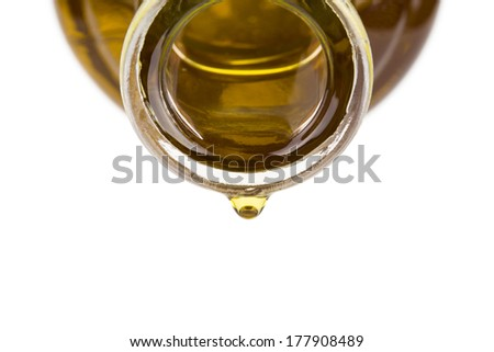 Oil drop on a bottle. Oil pouring from a bottle - stock photo
