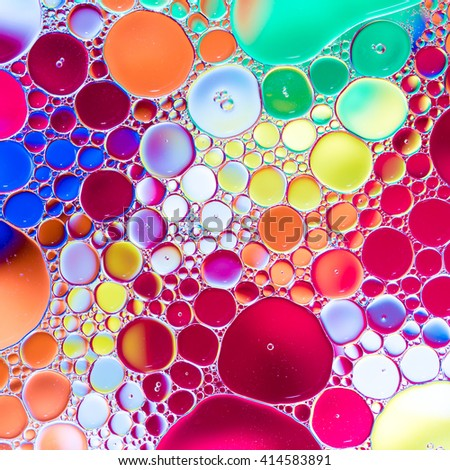 Oil drops in water on a colour background - stock photo