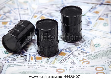 Oil drums on US dollars background - stock photo