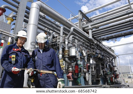 oil engineer, workers in front of large pipeline and fuel construction inside refinery - stock photo