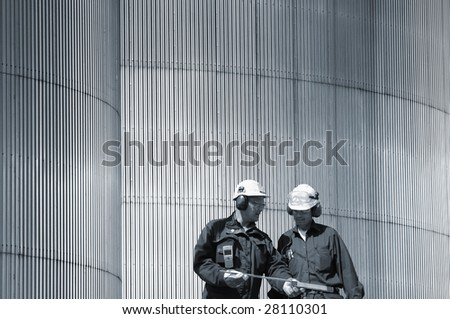 oil engineers in front of giant stainless-steel background, buish toning concept - stock photo