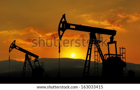 oil field and pump jack against sunset - stock photo