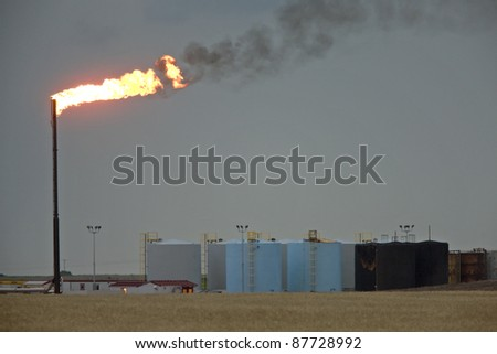 Oil Field  flame burn off gas oil jack well pump - stock photo