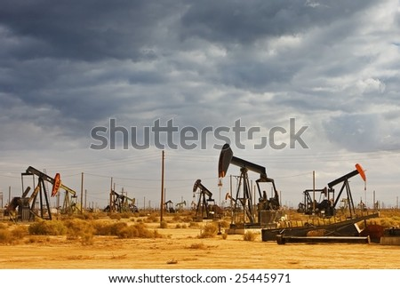 Oil Field in Desert with Dramatic Sky - stock photo